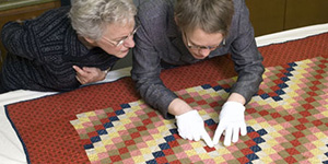 People inspecting a quilt