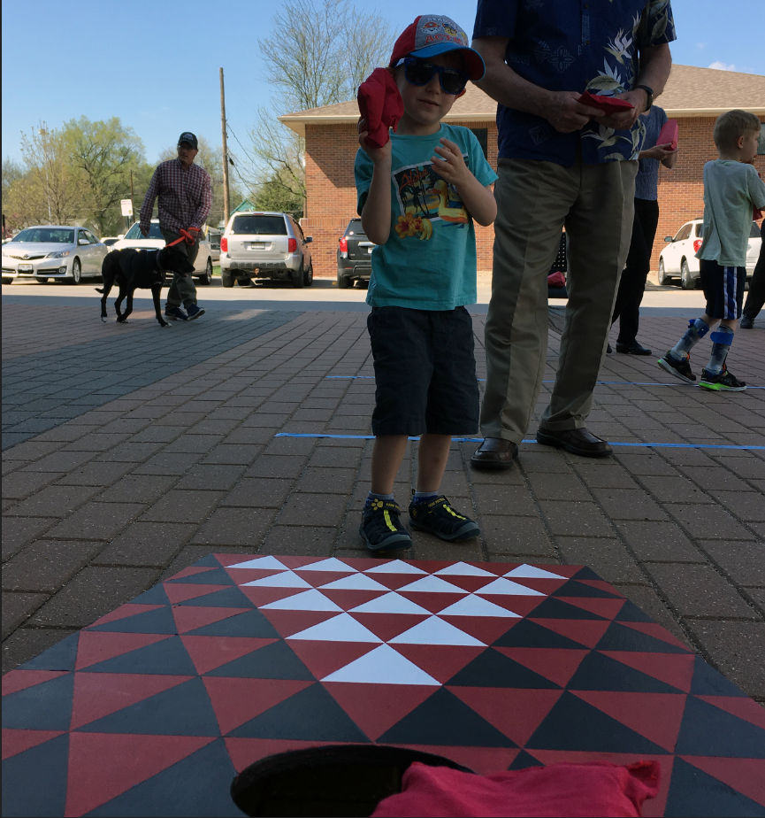 Child playing bean bag toss at a carnival.