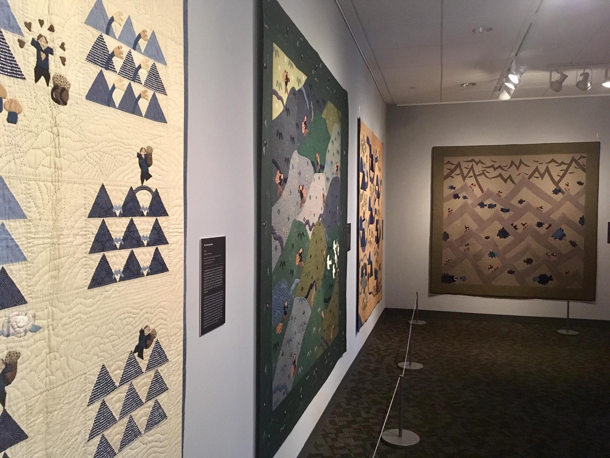 Three Rumi O'Brien quilts on display in a gallery.